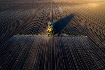 Tractor spraying soil in field