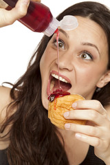 voracious young woman puts the topping on a donut on a white background