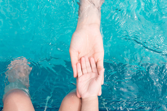 Child and adult hands underwater in the swimming pool