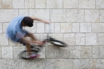 Cool free young biker in urban town jumping on bike on wall. Creative wallpaper background photo in grey and blue color. Static and dynamic background. Lifestyle of extremely fit man doing exercise.