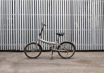 Retro vintage bicycle on factory with steel fence background. Industrial concept.