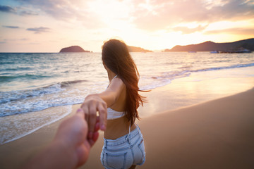 Couple holding hands on beach in sunset