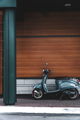vintage motor scooter parked in front of a building wall