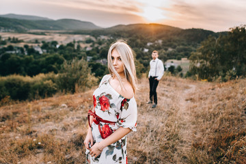 Portrait of a beautiful girl. A loving couple against the background of the mountains at sunset.