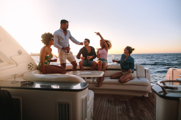Group of friends enjoying in a boat party Wall mural