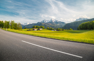 Empty asphalt country road with alpine mountain scenery in summer