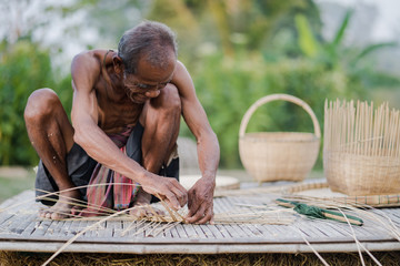Elderly man and bamboo craft, lifestyle of the locals in thailand