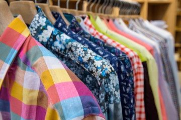 Multicolored men shirts hanging in the store.
