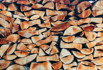 The chopped wood is packed in a woodpile. Firewood stacked on top of each other in rows. Wood stovemone background. Stack of wood