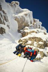 Group mountaineers on a safety enshrined station on the background of snow-covered rocks. Bottom view.  Tilt-shift effect.