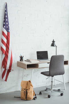 interior of modern living room with american flag on brick wall and table with laptop