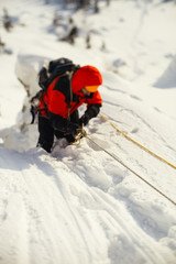 Mountaineer overcomes the complicated section on a snow-covered mountain slope.  Tilt-shift effect.