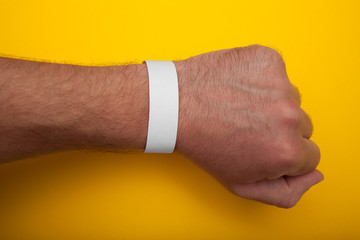 White wristband, bracelet mockup for event on yellow background.