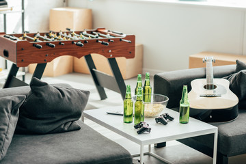 interior of modern living room with table football, beer bottles, joysticks and guitar