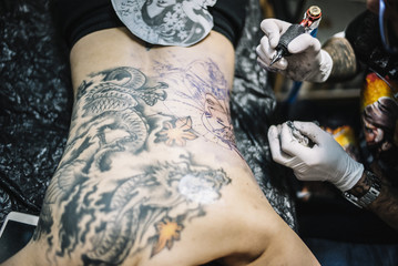 Master tattooing a back woman
