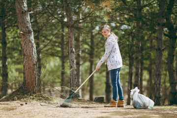 Young smiling beautiful woman cleaning and using rake for garbage collection near trash bags in park or forest. Problem of environmental pollution. Stop nature garbage, environment protection concept.