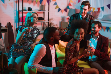 Multiracial smiling friends having party with drinks in decorated room