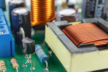 Transformer and electronic components installed on a printed circuit board closeup
