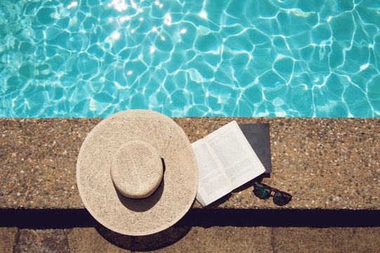 Book and hat at the pool side