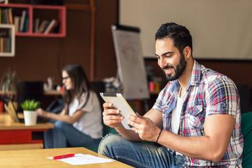 Portrait of bearded enterpreneur man using tablet computer for business sitting near table in modern office