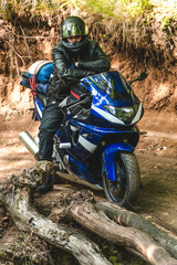 Fast sportbike motorcycle at forest dirt ground , adventure, road trip, lost navigation, another way, wrong turn, motorcyclist equipment, gear,
