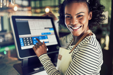 Smiling young waitress using a restaurant point of sale terminal
