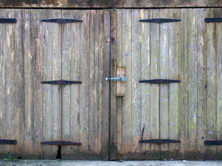 old rural grey plank wooden plank doors with a bolt fastening and rusty iron hinges