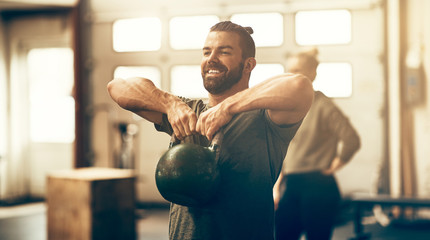 Fit young man smiling while lifting dumbbells in a gym