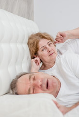 Irritated senior woman blocking ears while her husband snoring on bed