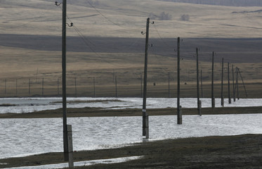 Electricity pylons are seen on the flooded banks of a lake in the Siberian village of Intikul