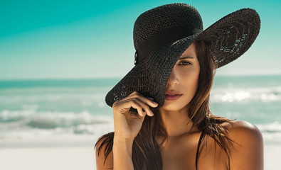 Fashion woman with straw hat at beach Wall mural