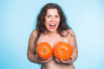 Young happy woman holds pumpkin in hands above her breast. Plastic surgery and silicone implants concept.