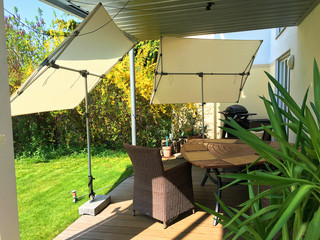 Two awnings protecting lounge area in a garden