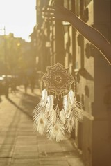 Handmade mandala God's Eye dream catcher with white peacock feathers and amethyst crystals on city background in Krakow