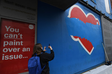 A woman takes a picture of a mural after director of the Project Arts Centre Cian O'Brien painted over a Pro-Choice 'Repeal the 8th Amendment' mural outside the Project Arts centre for a second time after being ordered by the Irish charities regulator to r