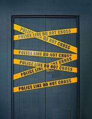 Crime scene closed door with yellow stripes text Police line do not cross