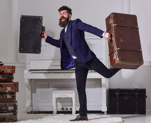 Man, traveller with beard and mustache with luggage, luxury white interior background. Hotel service concept. Macho elegant on cheerful face walks near pile of vintage suitcase, holds suitcases.