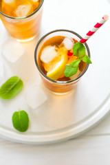 Glasses of iced tea with lemon slices and mint on white wooden background