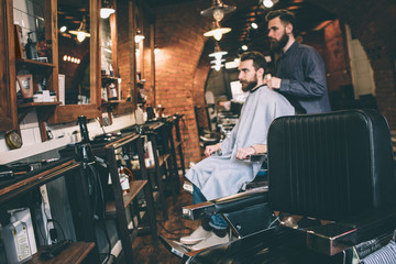 A picture from a distance. Guy is sitting in a chair and getting ready for cutting beard. His hairstylist is ready to start to work.