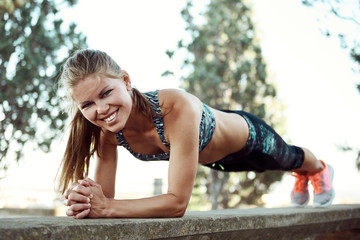 Pretty smiling female athlete standing in plank position outdoor. Sport, fitness and lifestyle.