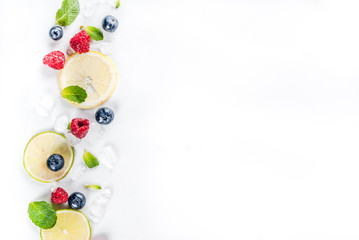 Healthy organic summer food and drink concept, selection of fresh fruit and berries, lime lemon raspberry blueberry pattern on white background copy space above top view
