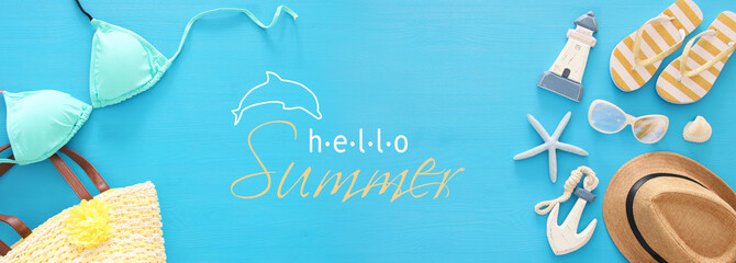 vacation and summer banner with sea life style objects and mint bikini over blue wooden background.