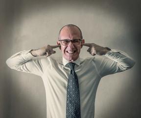 manager stressato con le dita nelle orecchie