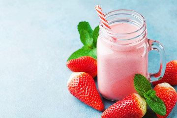 Red strawberry smoothie or milkshake in mason jar on blue table. Healthy food for breakfast and snack.