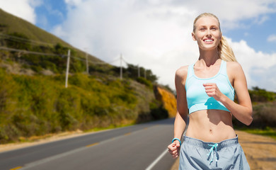 fitness, sport and healthy lifestyle concept - smiling woman running nearby road over big sur hills and road background in california