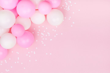 Pastel pink table with colorful balloons and confetti for birthday top view. Flat lay style.