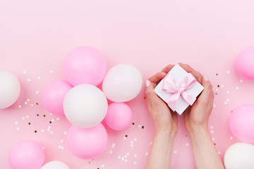Womans hands holding gift or present box on pink pastel table decorated balloons and confetti. Flat lay style.