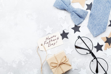 Happy Fathers Day background with paper tag, gift, glasses, necktie and bowtie on stone table top view in flat lay style.