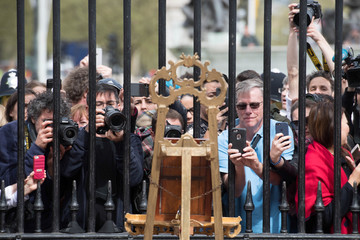 Tourists and photographers take pictures of a notice placed on an easel in the forecourt of Buckingham Palace to formally announce the birth of a baby boy to the Britain's Catherine, the Duchess of Cambridge, and Prince William, in London