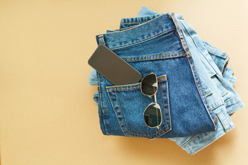 Picture of two jeans with mobile in pocket and glasses on craft wooden background